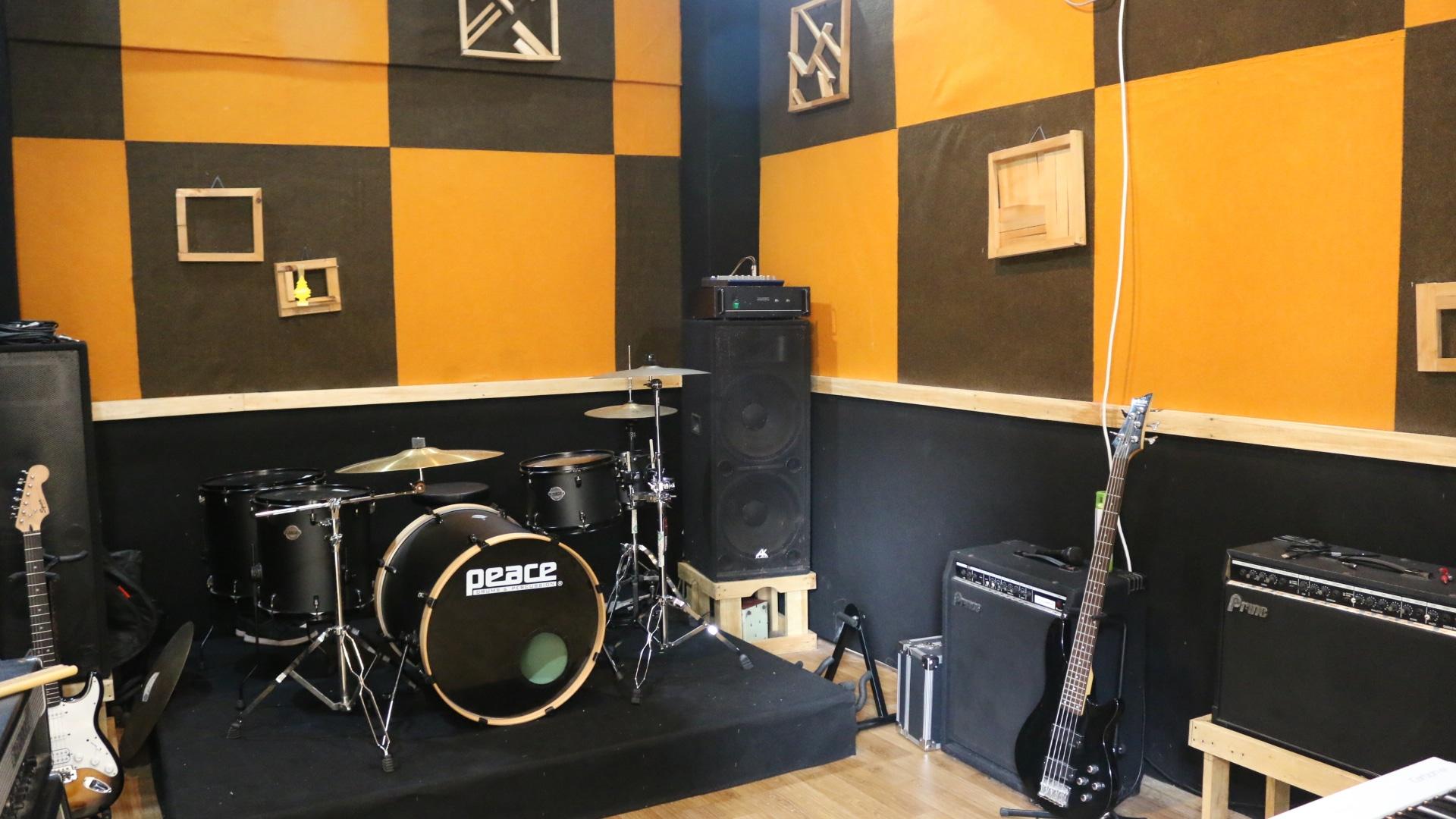 Studio Musik Dengan Alat Musik Gitar Elektrik, Gitar Bass Elektrik, Drumset, Speaker Amplifier, dan Audio Effect